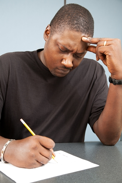 African-american adult education student struggles with test anxiety as he takes an exam.